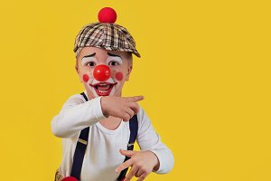 Child clown smile shows a finger copy space area on yellow background. Funny little clown with red nose. Concept birthday, day 1 april, party. Beautiful portrait kid jester in studio.