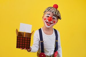 Funny kid clown isolated on yellow background. Beautiful playful portrait child boy jester in makeup. Expression face joy, smile, fun, cheerful. 1 April Fool's day concept.