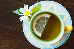 Cup of herbal tea with chamomile and lemon on the wooden background