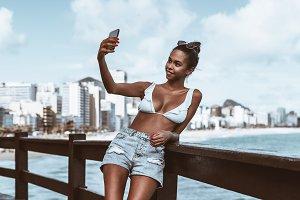 Black girl taking selfie near beach