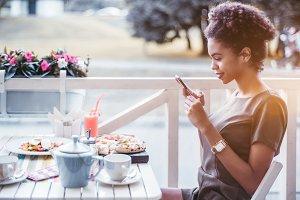 Black girl is taking pics in cafe