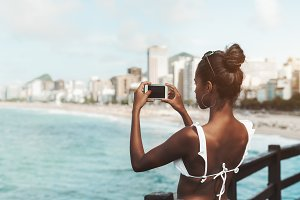 Black girl photographing seascape