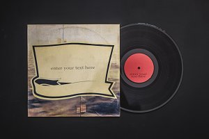 overhead flat lay of blank vinyl record out from the cover with place for text copyspace on black table mockup