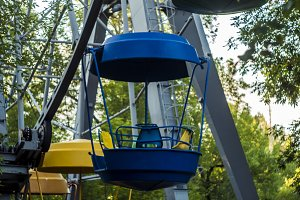 single blue ferris wheel cabin in the amusement park