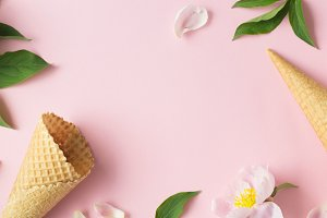 Spring or summer mood concept. Flat-lay of waffle sweet cone with berryy over pastel light pink background, top view.