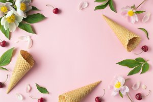 Flatlay of cerry, sweet cones and peonies over pastel pink background. Top view with space for your text