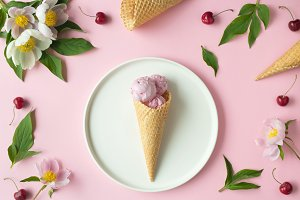 Flatlay of pink ice cream scoops, cerry, sweet cones and peonies over pastel pink background. Top view with space for your text