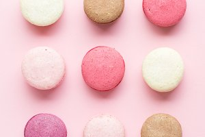 Colorful cake macaron or macaroon isolated over pastel pink background. Top view