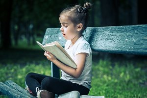 little girl is sitting on a bench