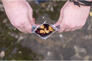 A man holds a package with a snack. A mix of nuts.