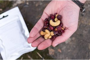 A set of dried berries and nuts in the palm of your hand. Cashew and cranberry