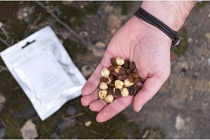 Hazelnut and almonds in the palm of your hand. A man is holding a mix of nuts.