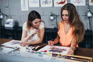 Two adult female students working on their paintings studying at art school