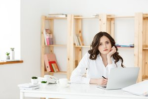 Tired beautiful Businesswoman holding hand on head while working on computer and some business documents in bright office