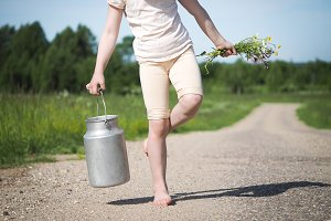 Children's legs, milk can and wildflowers