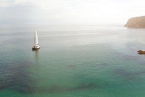 Panoramic view of Pacific Ocean blue transparent water, a white sport modern luxury yacht sail boat floating and a green shore with forest, hills. Holiday by the water and sail race.