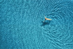 Aerial view of swimming woman in the sea at sunset in Maldives
