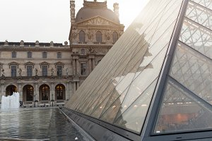 PARIS, FRANCE. 01 June 2018: Louvre Museum square with summer sunset. The old renaissance building is enlightened by the sun and the glass pyramid is standing in the middle.