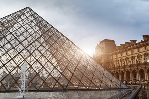 PARIS, FRANCE - June 01, 2018: View of famous Louvre Museum with Louvre Pyramid at evening sunset. Louvre Museum is one of the largest and most visited museums worldwide
