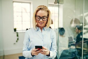 Smiling businesswoman standing in an office using a cellphone