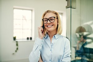 Businesswoman smiling and talking on her cellphone in an office