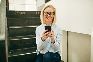 Businesswoman smiling while sitting on office stairs reading a text