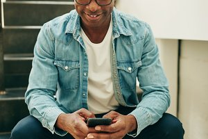 Young African businessman sitting on office stairs reading text messages