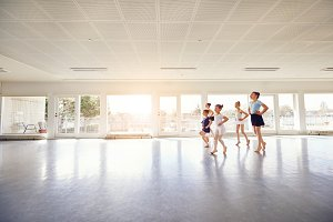 Group of little ballerinas performing ballet dance in class