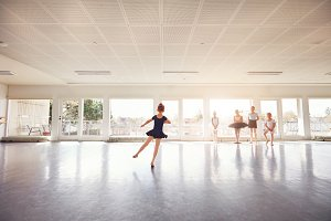 Little girl dancing ballet while group watching