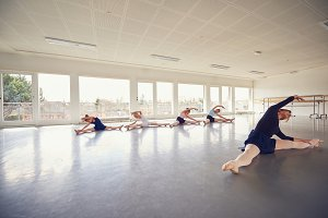 Teacher bending and stretching with children ballet group in class