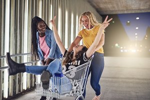 Laughing young girlfriends playing with a shopping cart at night