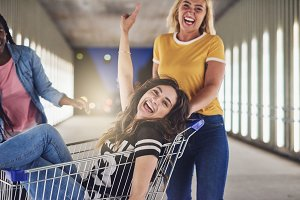 Girlfriends playing with a shopping cart together in the city