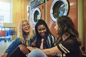 Diverse young girlfriends sitting together on a laundromat floor talking