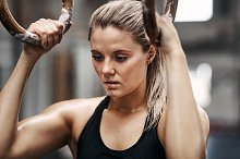 Fit woman preparing to workout with rings in a gym by  in Sports