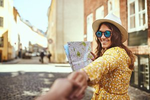 Smiling woman holding a map leading someone through city streets