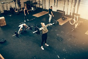 Fit people working out with weights in a gym class