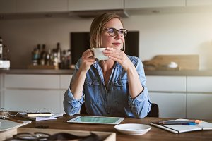 Smiliing woman drinking coffee while working online from home