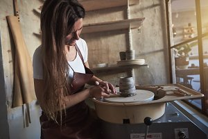 Female artisan creatively turning a clay vase in her workshop