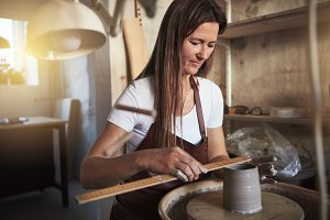 Female artisan measuring a clay vase in her pottery workshop