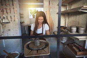 Artisan shaping clay on a pottery wheel in her studio