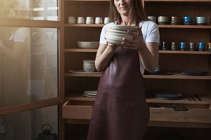 Creative artisan inspecting new plates in her pottery studio
