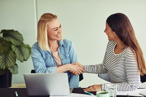 Smiling businesswomen sitting at an office table shaking hands together