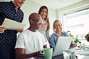 Diverse businesspeople smiling while working online together in an office