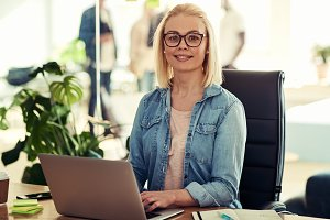 Confident young businesswoman working at her desk in an office
