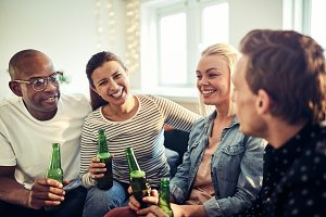 Laughing young businesspeople drinking beers after work in an office