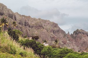 Local stone dwellings surrounded by tropical vegetation. Sharp mountain formation rising on the background. Santo Antao Island, Cape Verde