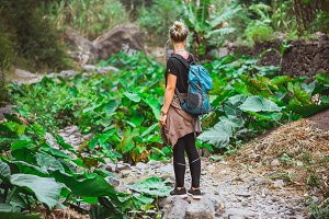 Girl admire the lotus plants on her way in lush green valley of the mountains. Santo Antao. Cape Verde