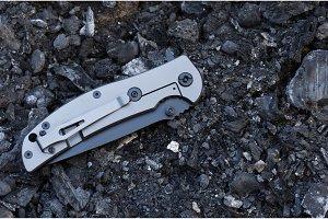Aluminum handle and clip. Folded knife. Black stones.