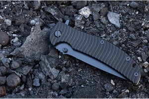 The knife is in a folded position. Black handle. A knife on the rocks.