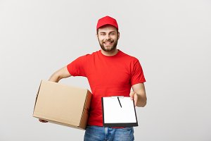 Delivery Concept: Young handsome delivery man with paper boxes giving you a document to sign